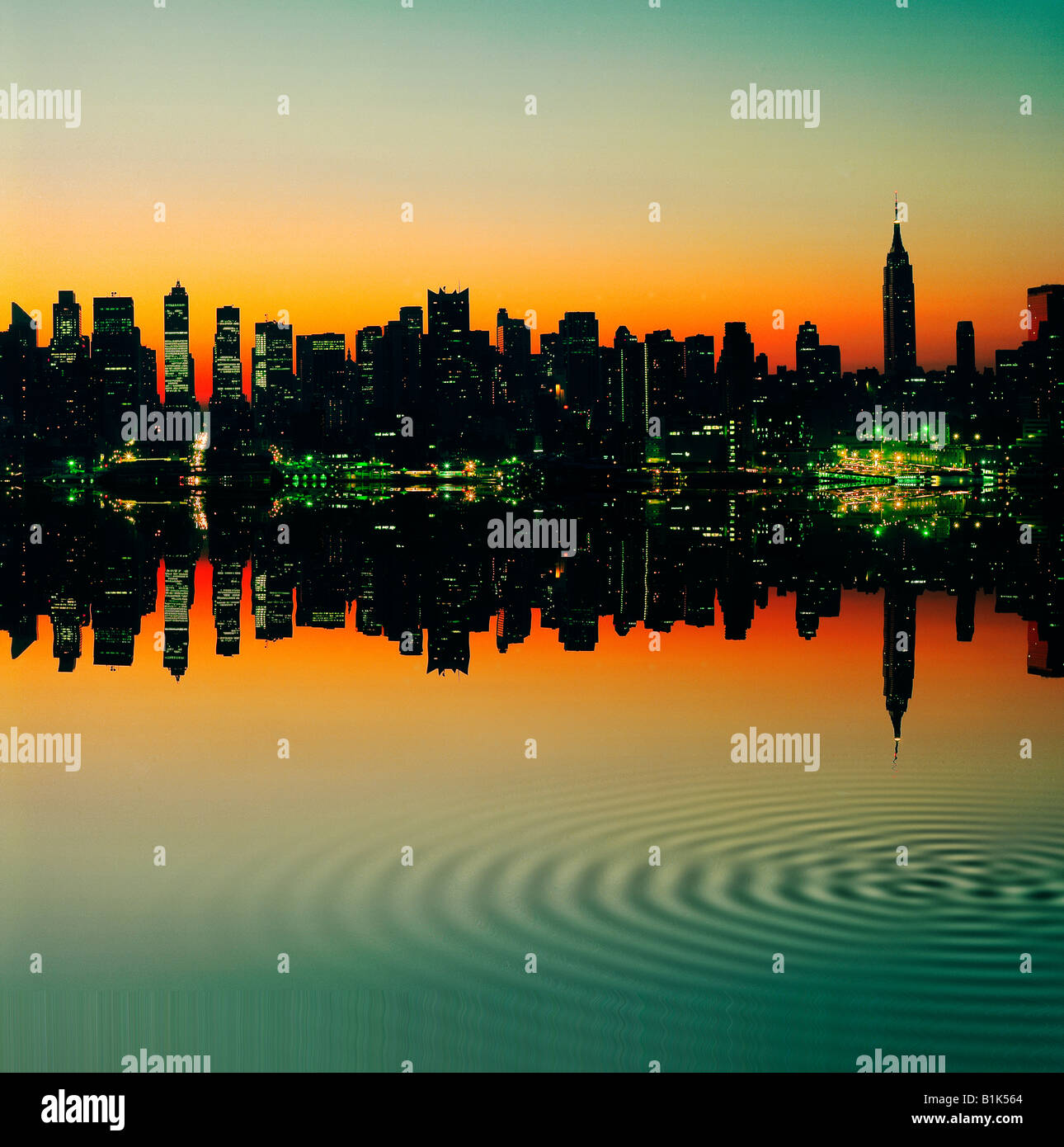 Empire State Building and New York skyline at sunset reflected in East River - Stock Image
