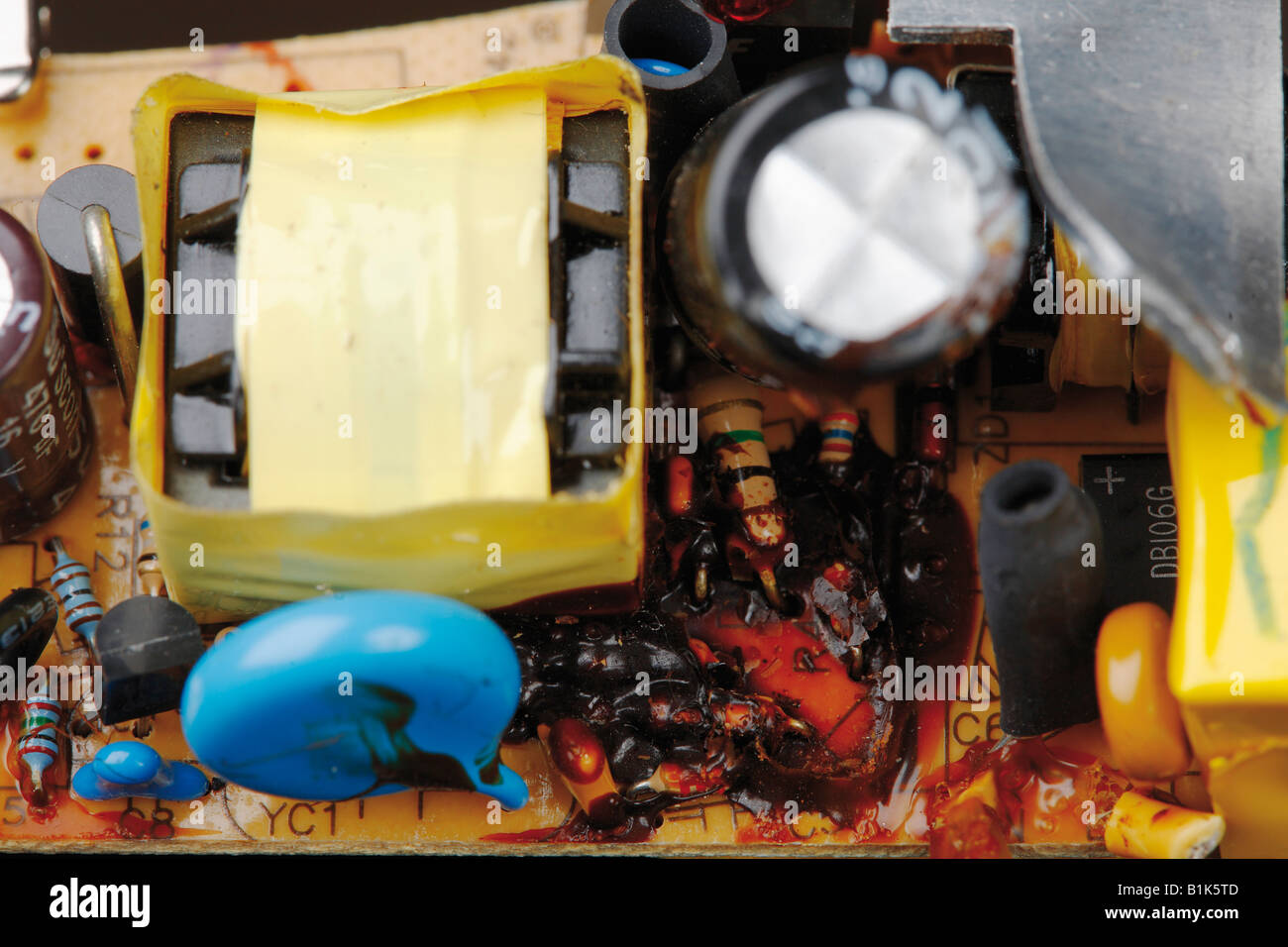 Broken circuit board with bursted capacitor - Stock Image