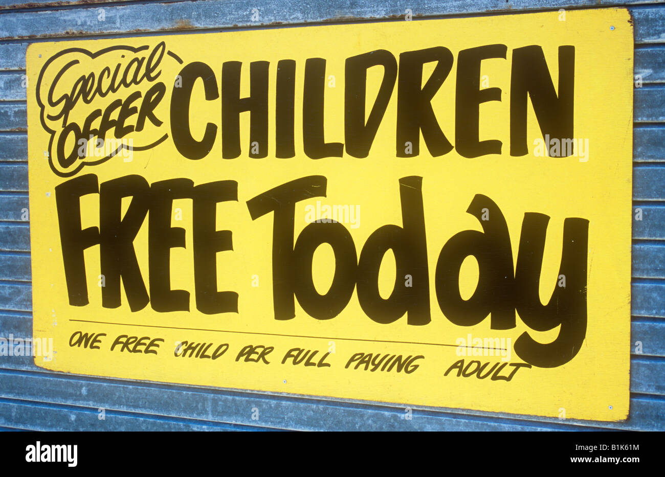 Signwritten notice black on yellow Special offer Children free today then in small writing One free child per full - Stock Image