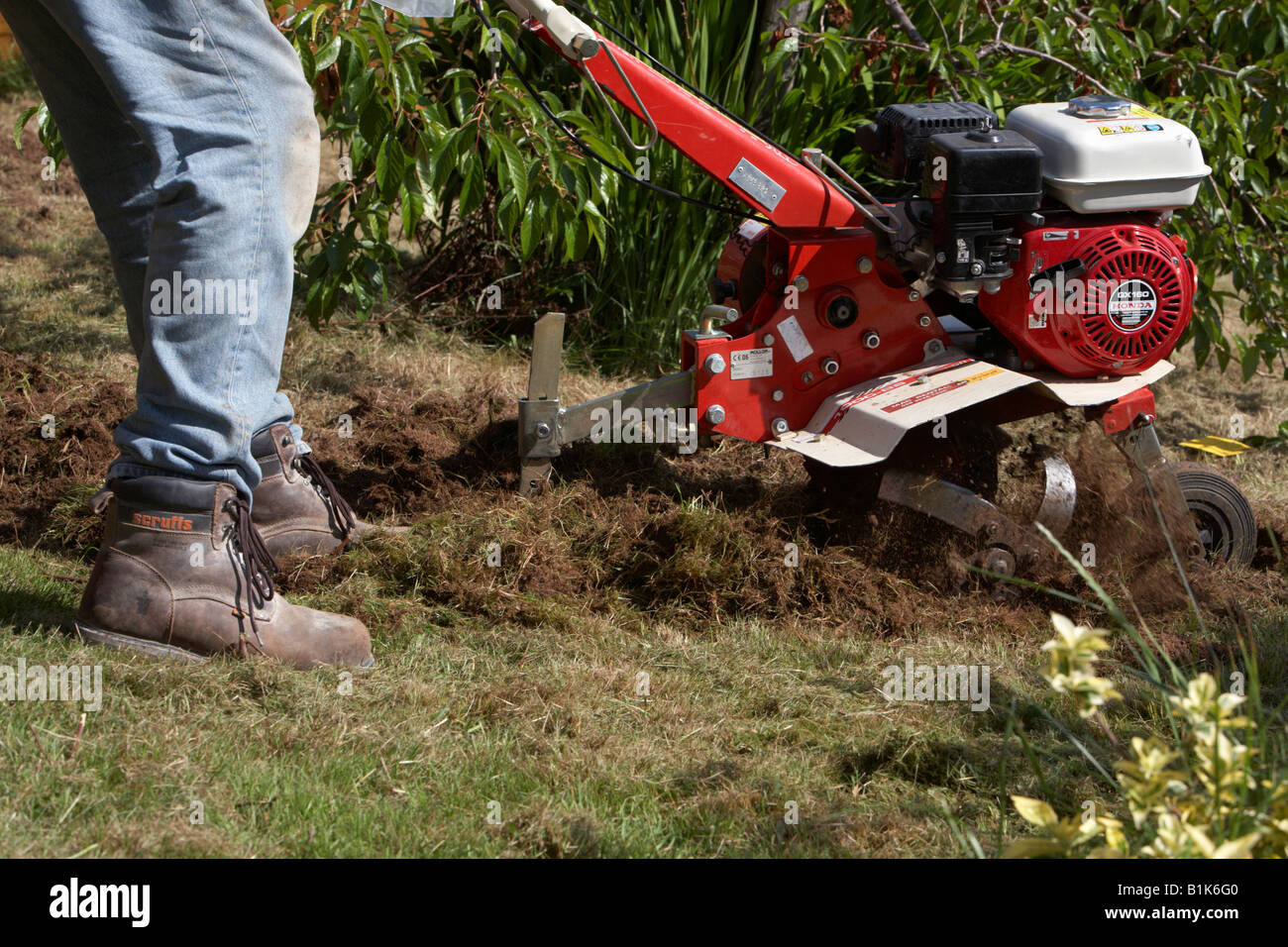 man wearing jeans and safety boots operates petrol driven garden ...