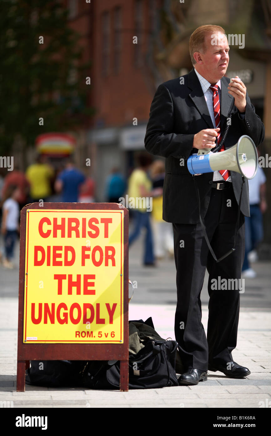 male christian fundamentalist preacher with loudspeaker and bible verse on sign on sunny afternoon in main shopping Stock Photo