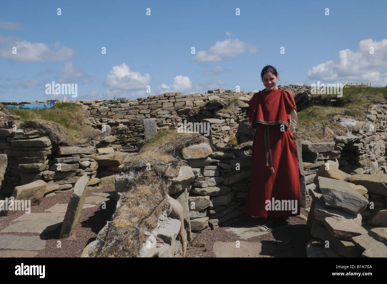 A guide at the 2,500-year-old settlement at Scatness, Shetland wears historically accurate Viking dress. - Stock Image