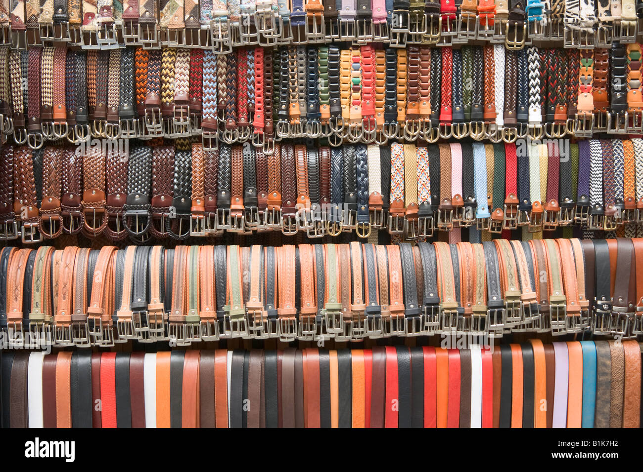 Belts hang down in a row for sale, Florence, Italy - Stock Image