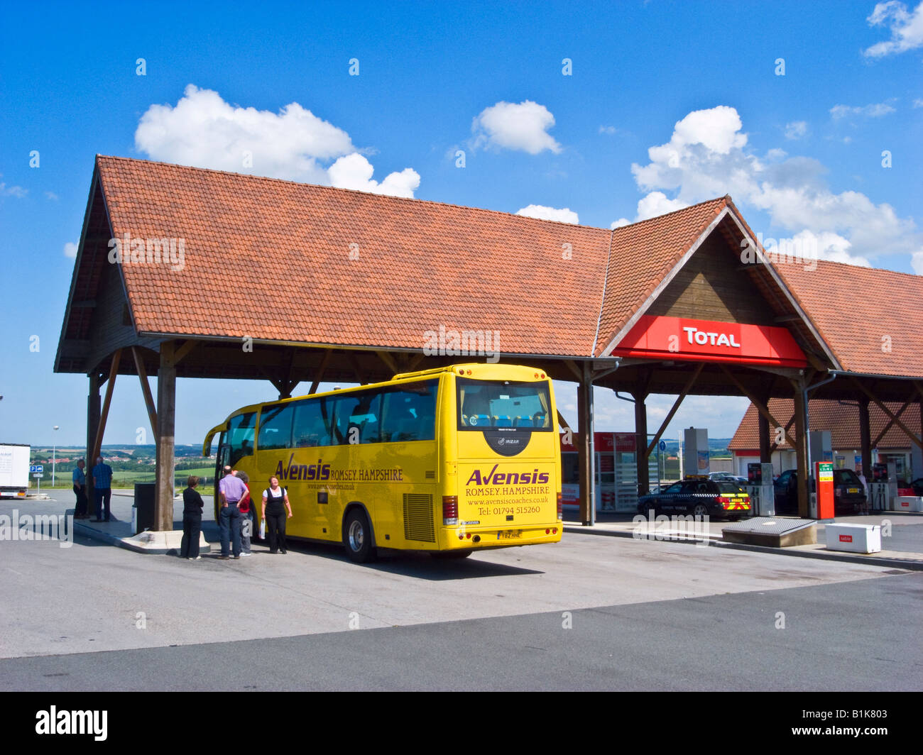 Refuelling stop for a British tour coach in France near Calais - Stock Image