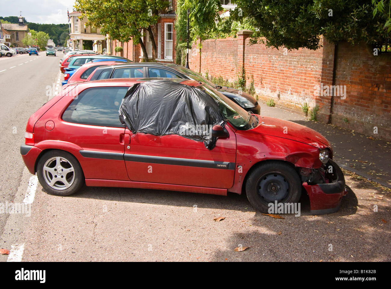 Red private saloon car damaged and parked by roadside in Stockbridge Hampshire UK - Stock Image