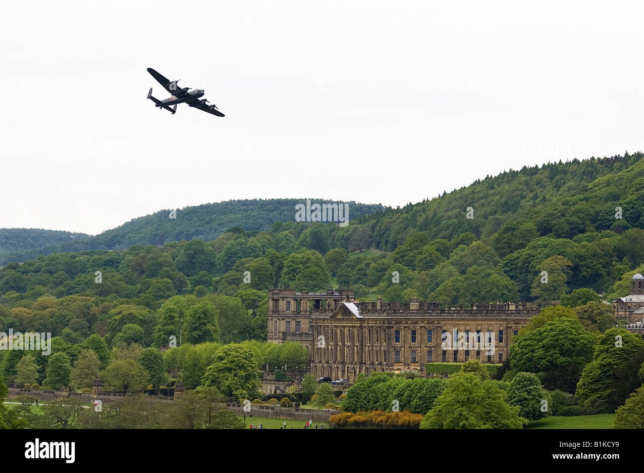 A Lancaster RAF Bomber makes a flypast over Chatsworth House home to the Duke of Devonshire - Stock Image