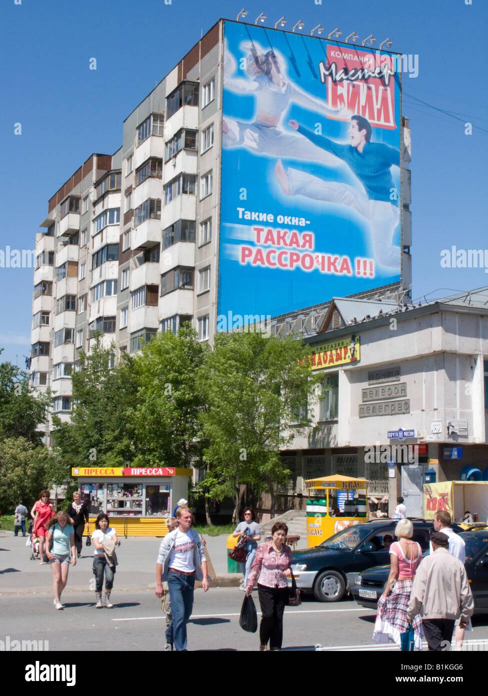 Contrast of large modern advertising billboard on old soviet era apartment block in Yuzhno Sakhalinsk Sakhalin Russia - Stock Image