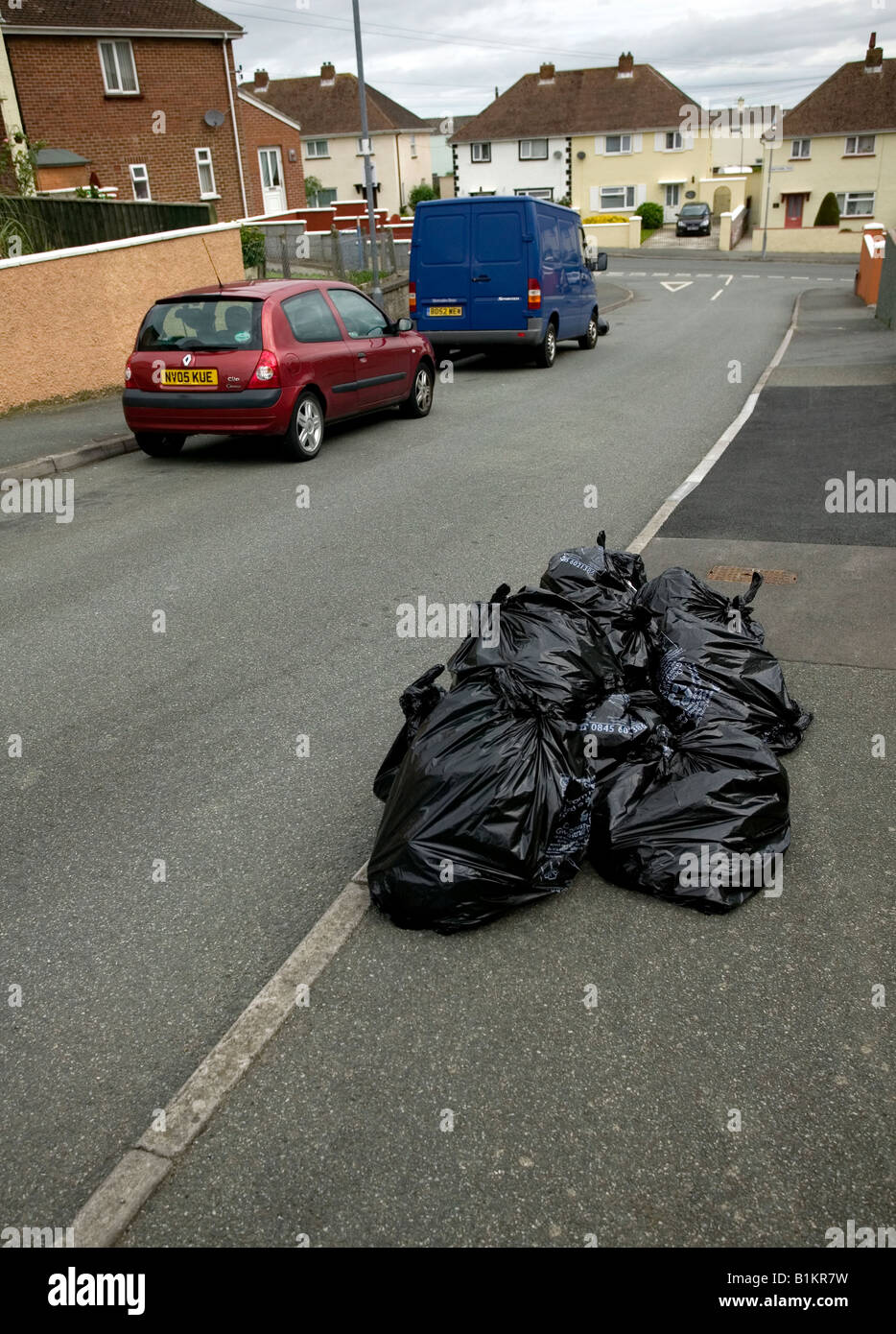 Plastic Rubbish bags waiting for collection on UK street - Stock Image