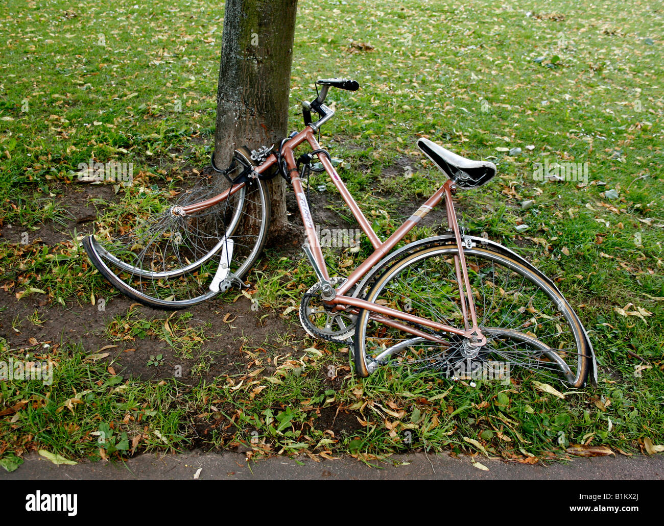 A bicycle has been abandoned, possibly due to a crash and lies broken and neglected. - Stock Image