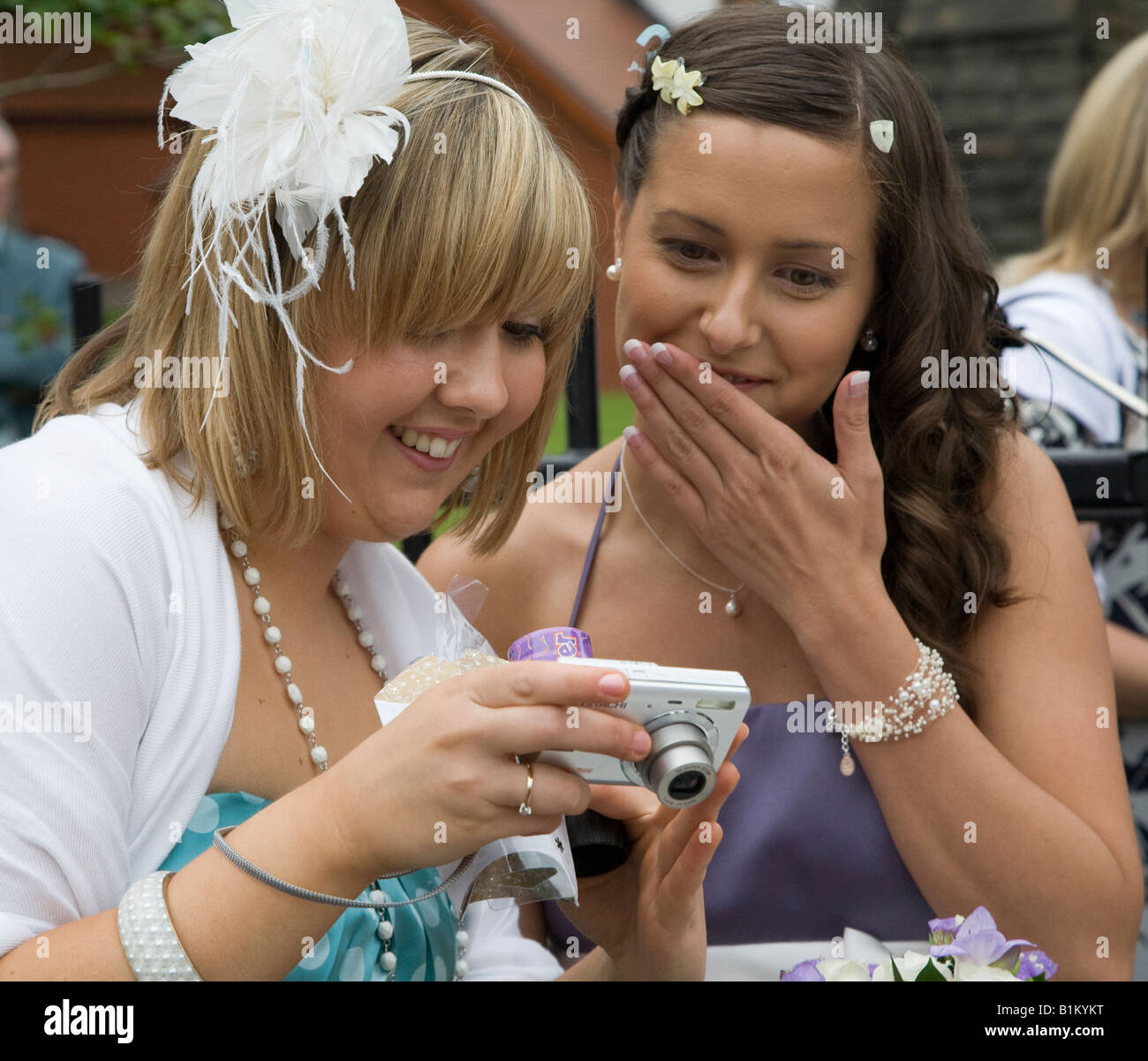 Wedding guests looking at digital photos on camera Wales UK Stock Photo