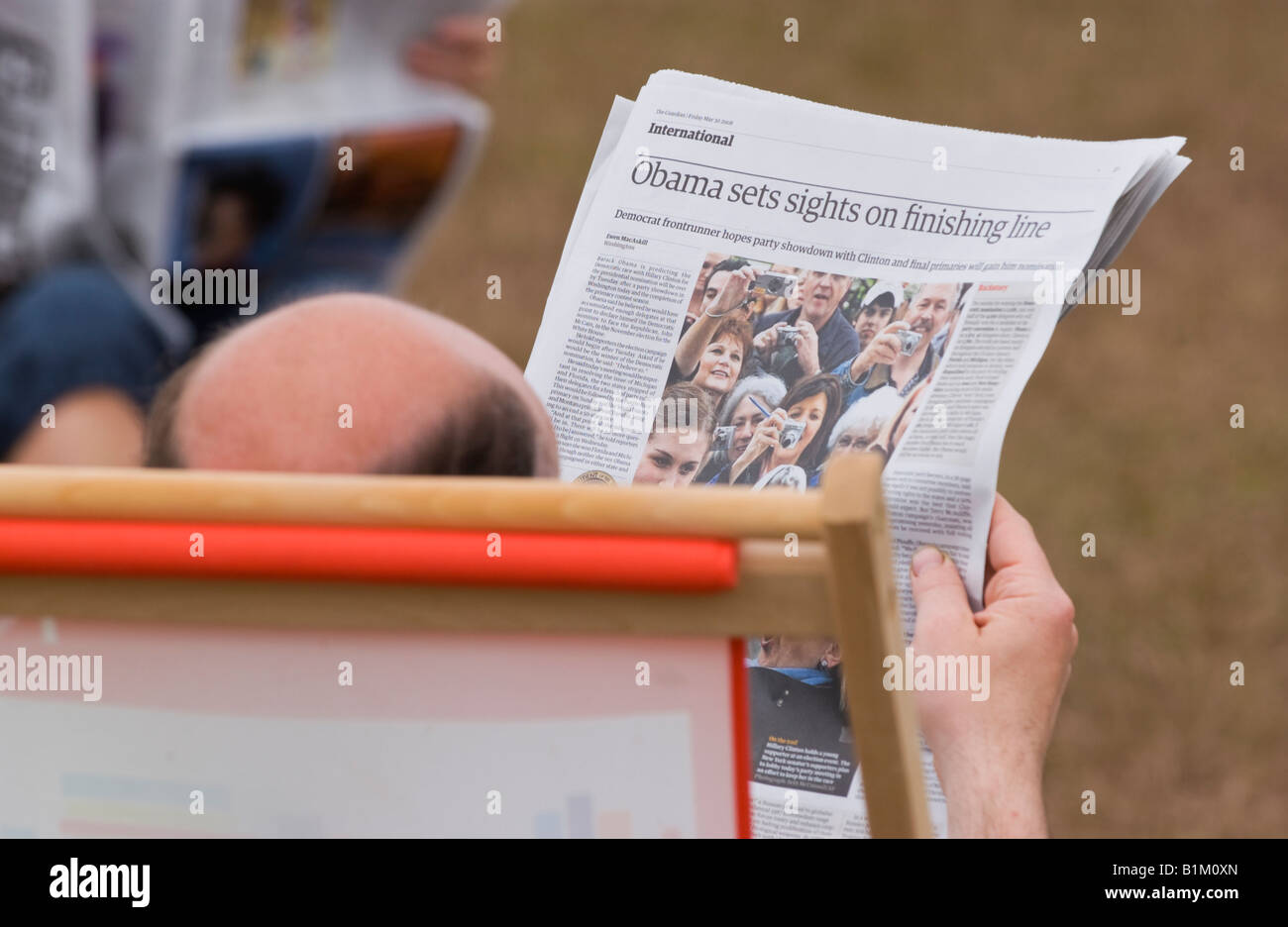 Bald man sat in deckchair reading newspaper at The Guardian Hay Festival 2008 Hay on Wye Powys Wales UK EU - Stock Image