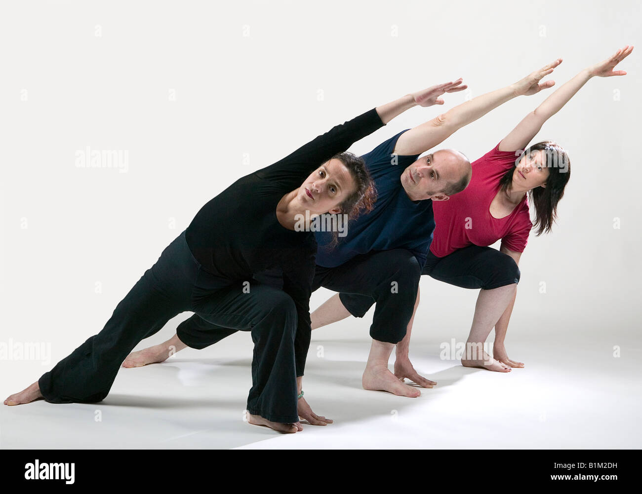 three people practicing yoga variation of the triangle pose stock