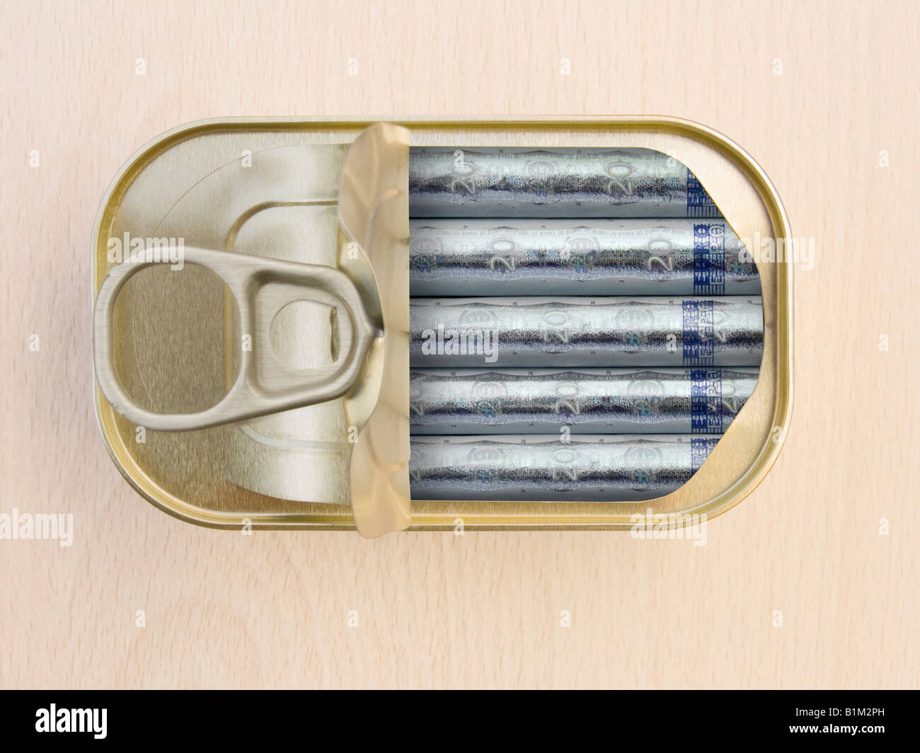 Plan view of a Ring Pull Tin containing rolled 20 Euro notes on wooden surface - Concept Stock Photo