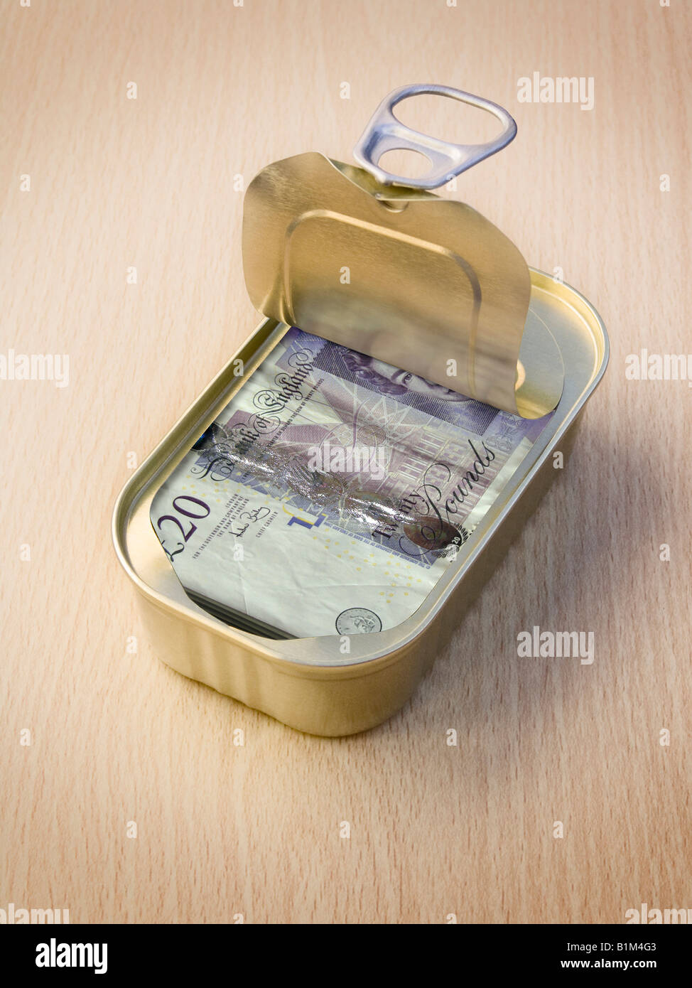 Ring Pull Tin containing £20 notes on wooden surface - Stock Image