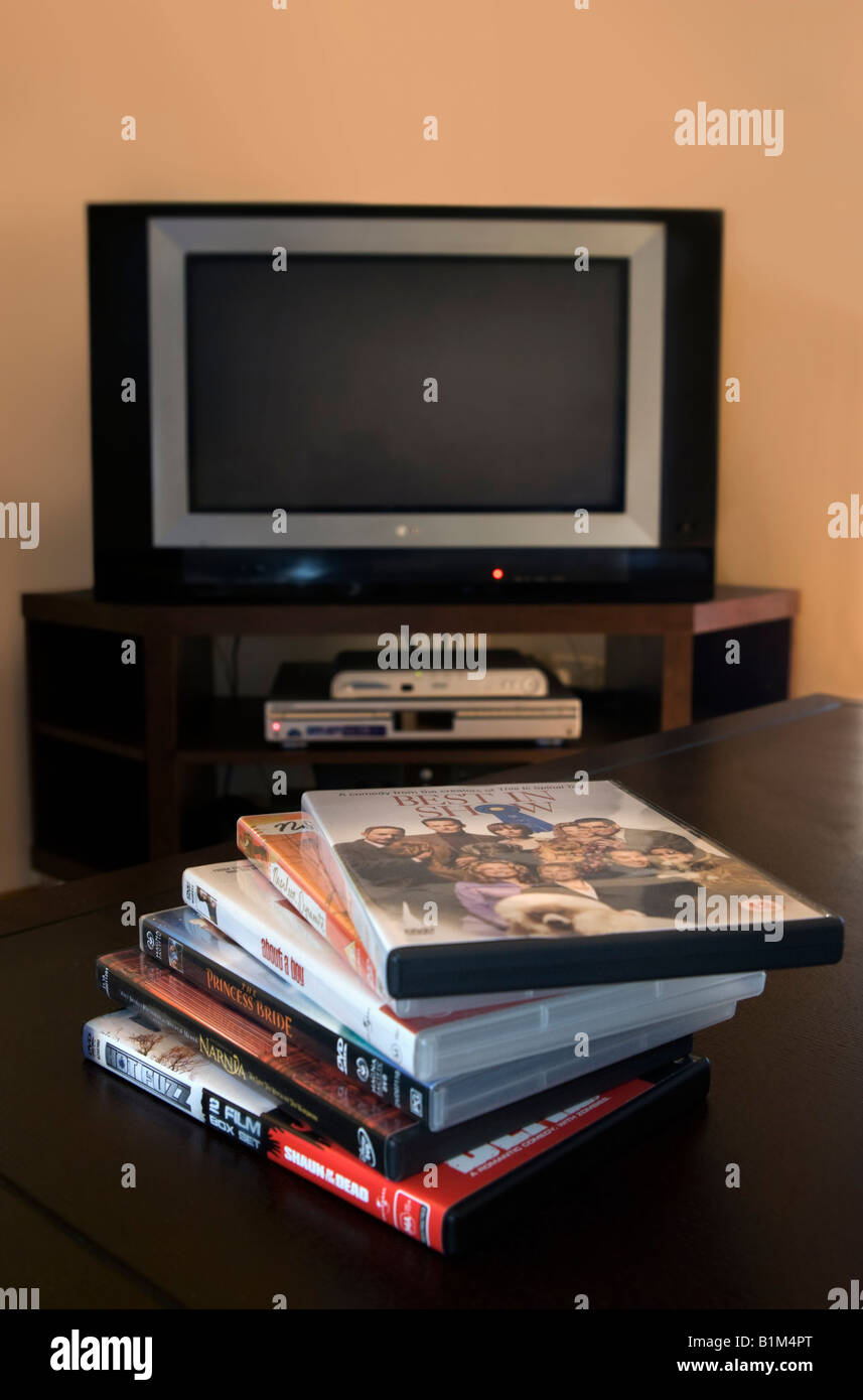 A pile of DVD movies with a television and DVD player in the background - Stock Image