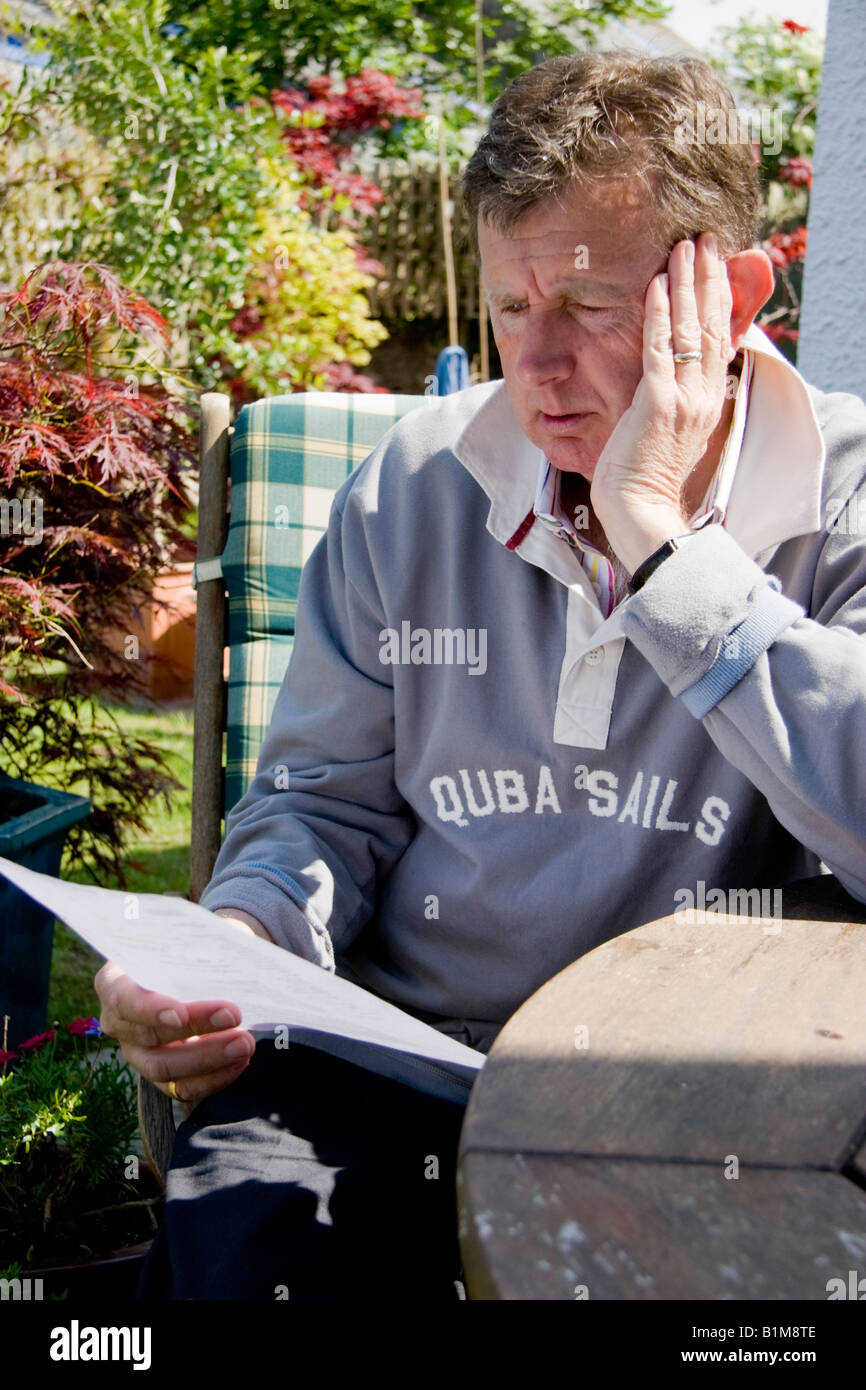 Mature man sitting at a table and reading paperwork - Stock Image