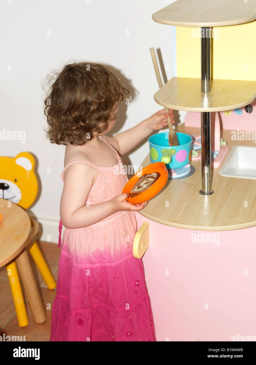 Three Year Old Girl Pretend Cooking - Stock Image