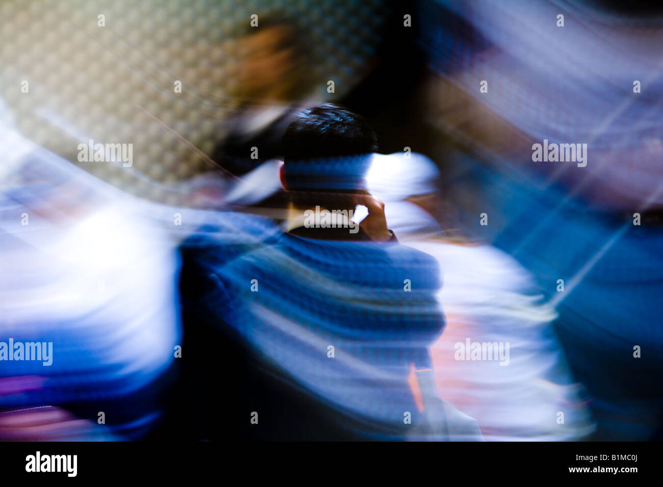 Business man in motion on the phone at a BART station. - Stock Image