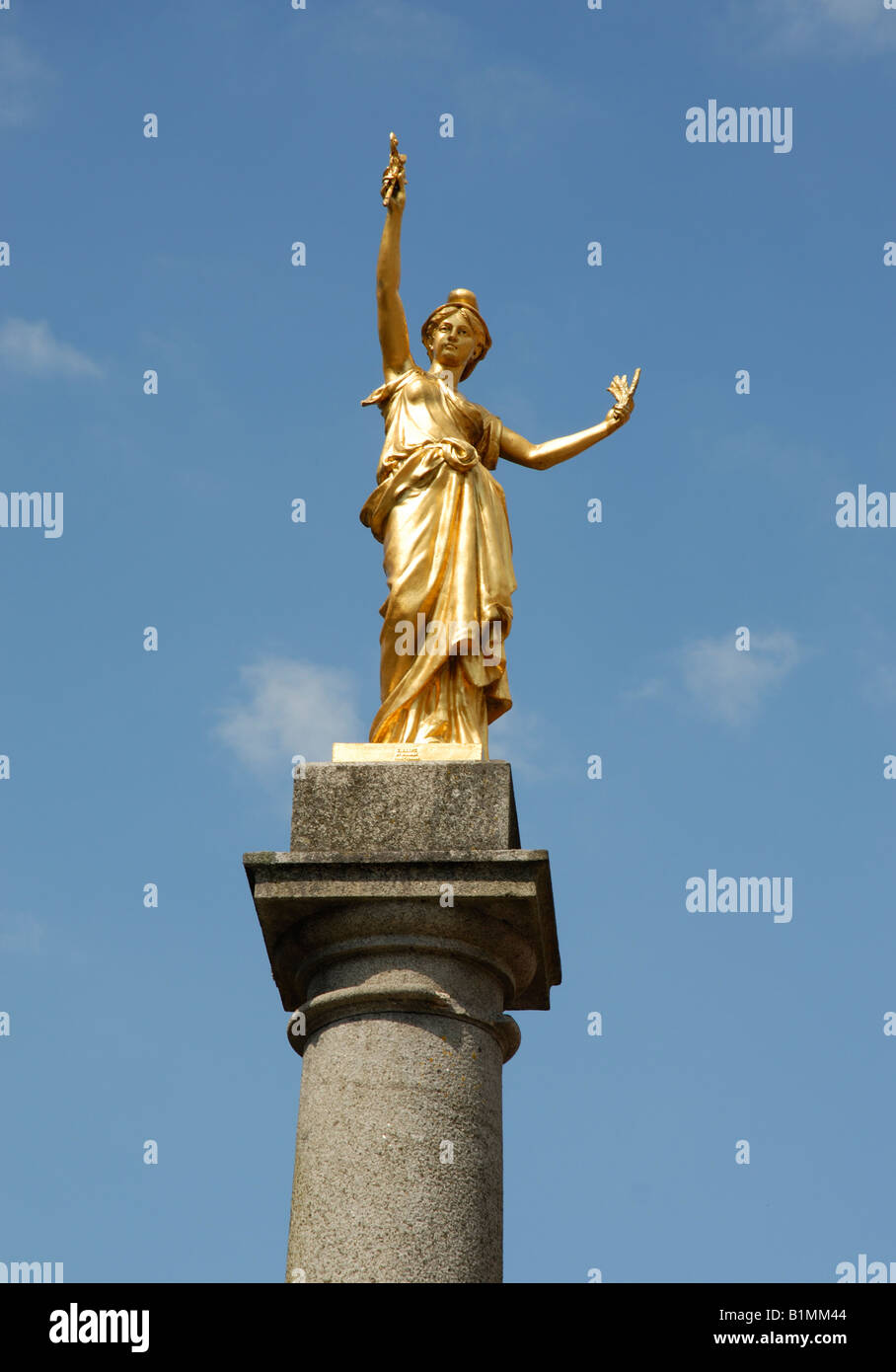 A guilded statue of Francoise,  looks down from her column on the 'Place de la Republique' in Villedieu - Stock Image
