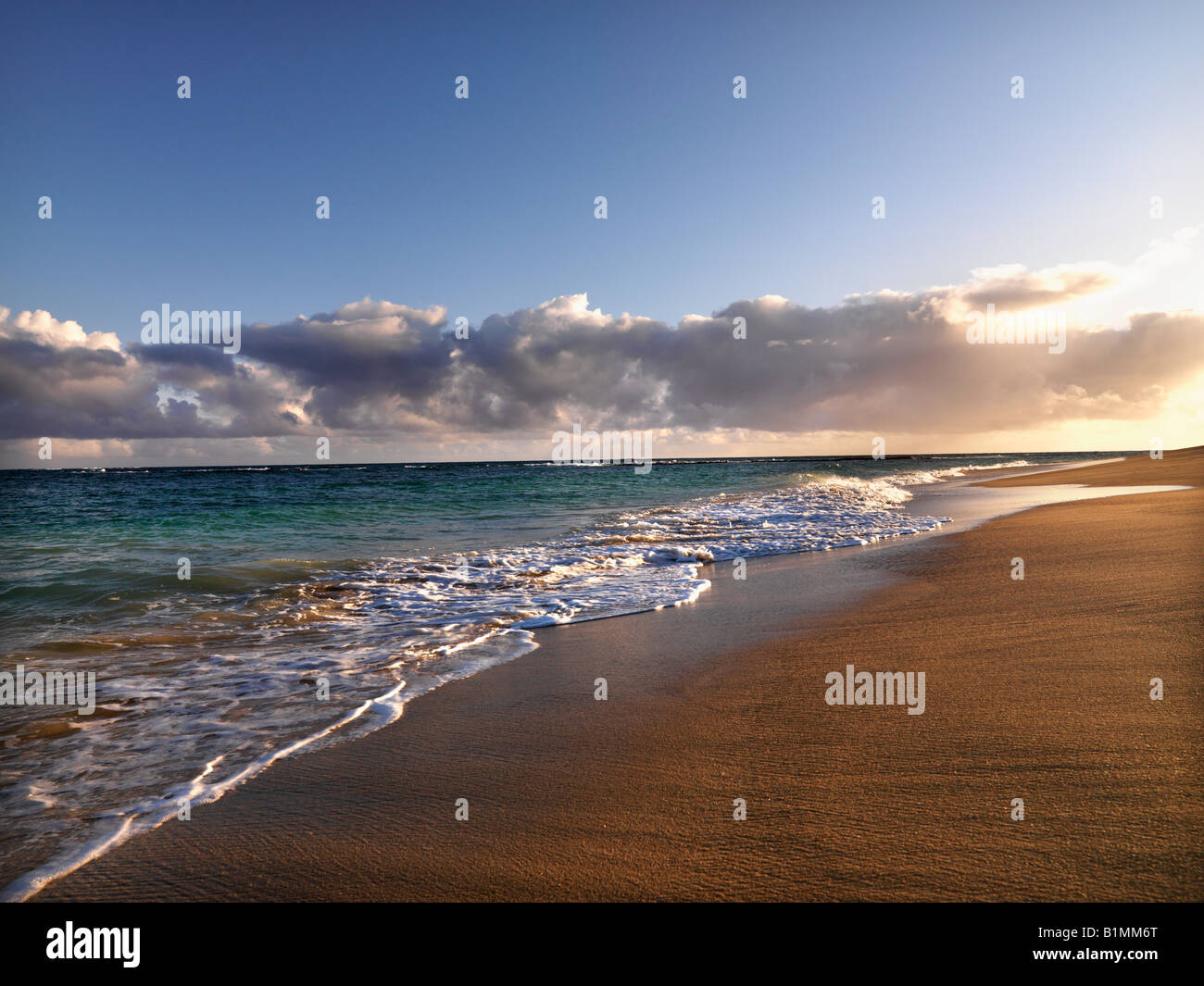 Waves lapping on the beach at dusk in Maui Hawaii - Stock Image