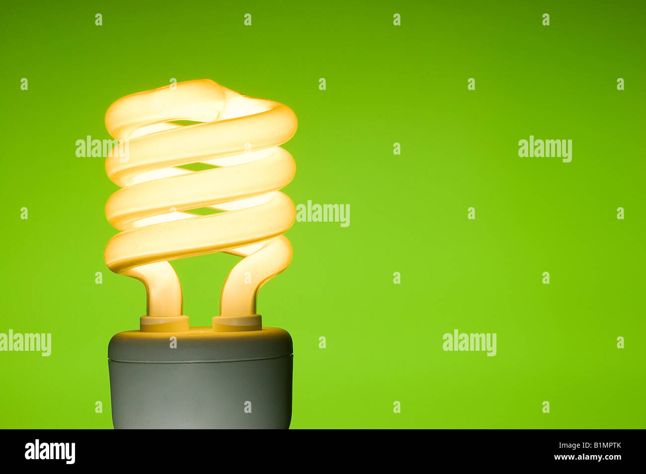 Energy saving fluorescent light bulb on green background Space for ...