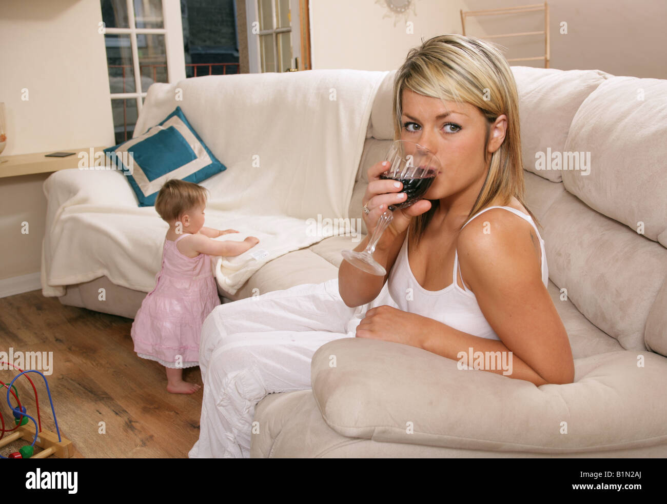 A young mother with her 9 month old child. - Stock Image