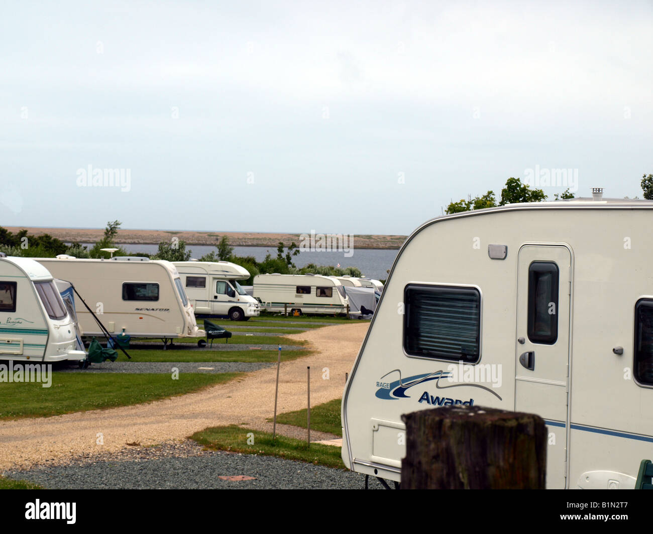 The east fleet caravan park,with the fleet lagoon and chesil beach in the background at fleet,weymouth,dorset,uk. - Stock Image
