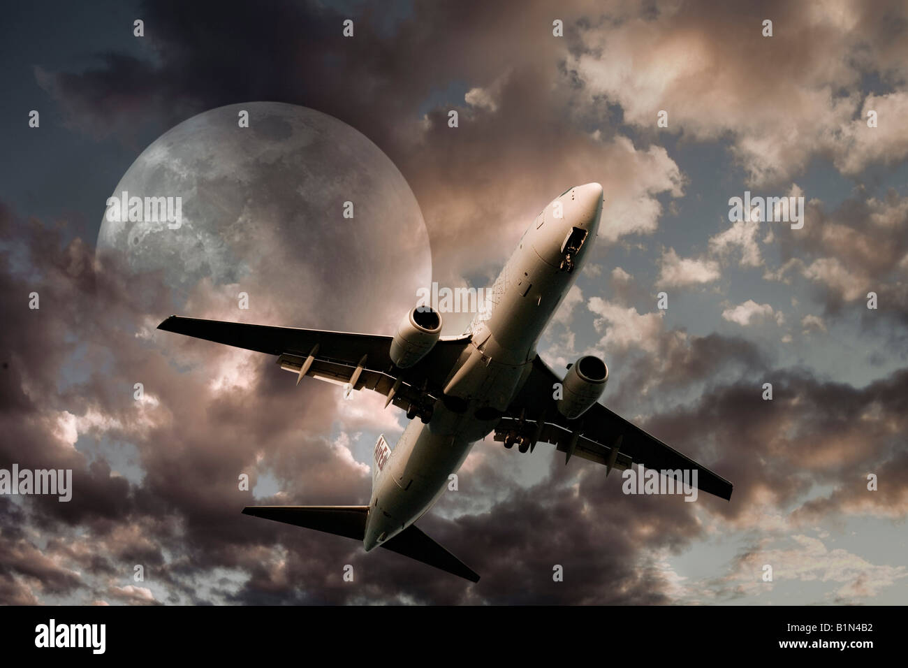 Airplane take off against a full moon - Stock Image