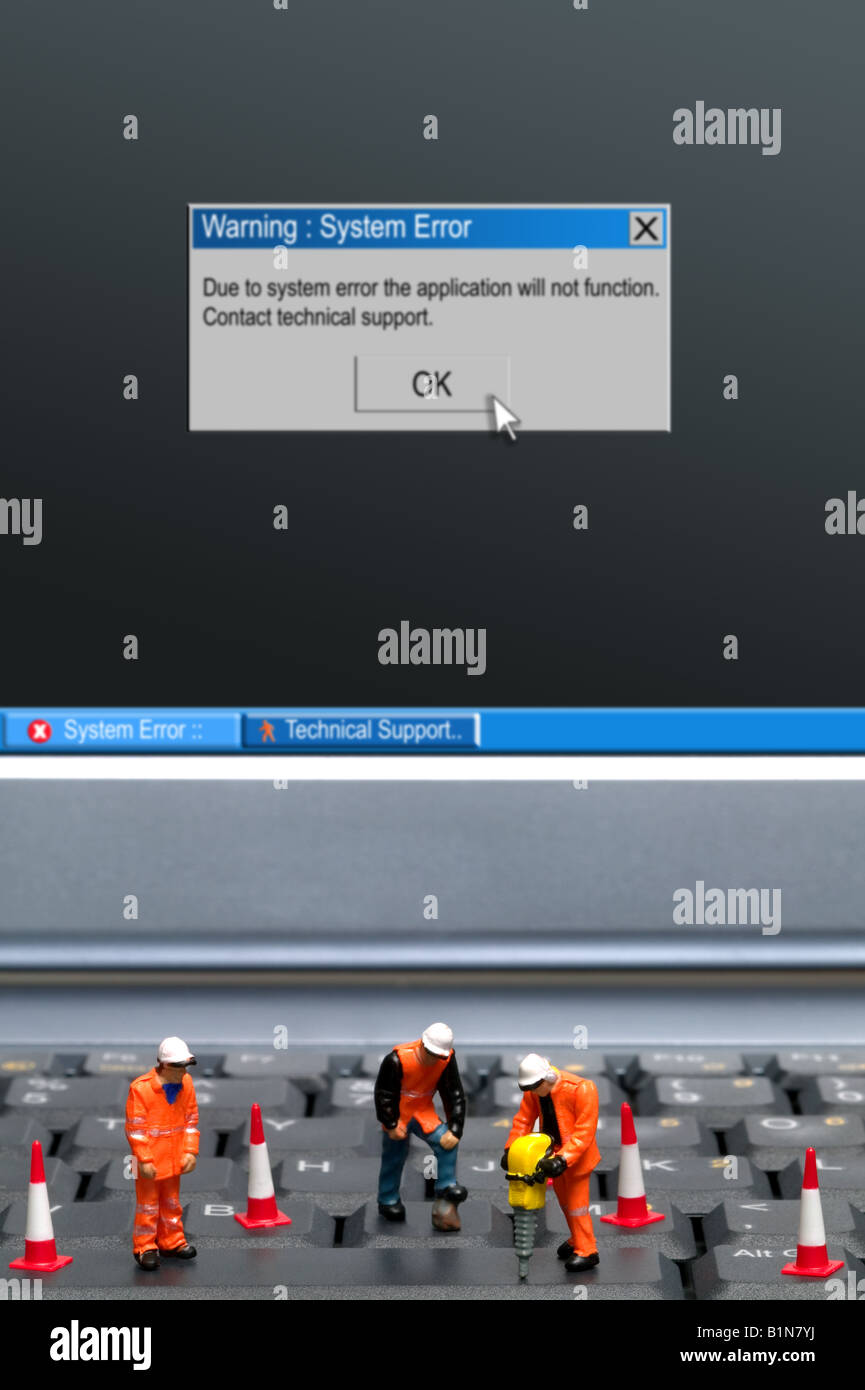 Miniature workmen repairing a computer keyboard system error message on the screen part of a series of images along - Stock Image