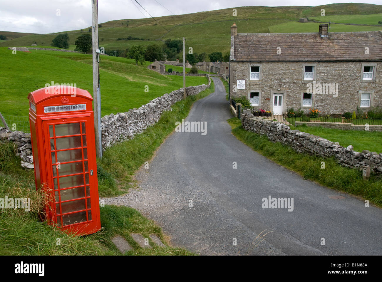 Stone houses, walls and red phonebox, Keld Village, Swaledale, Yorkshire Dales National Park - Stock Image