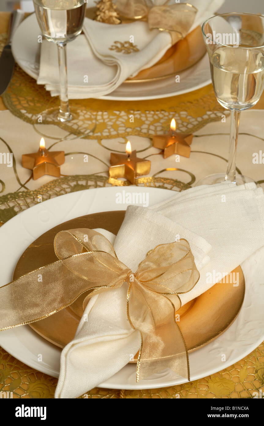 Christmas table place setting, napkin tied with a golden ribbon ...
