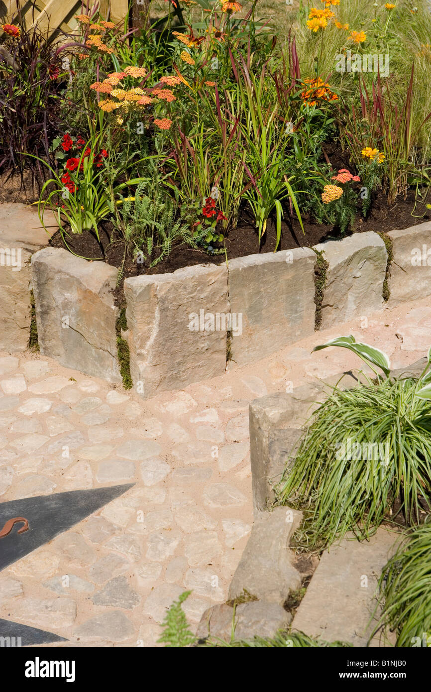 paved path with raised flower beds for easy access - Stock Image