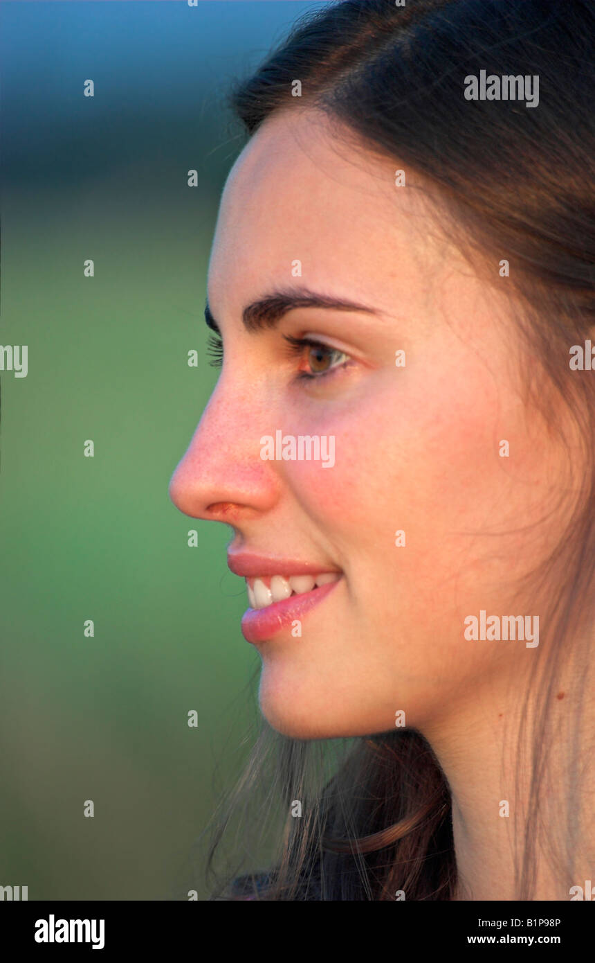 Profile of a beautiful young woman outdoors looking away - Stock Image