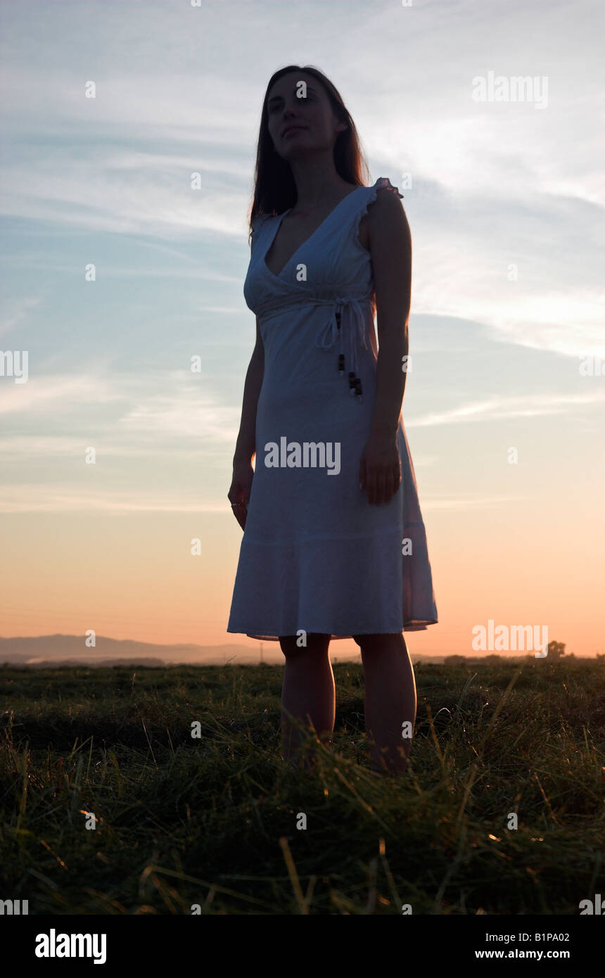 Silhouette of a young woman wearing summer dress standing in field at dusk - Stock Image