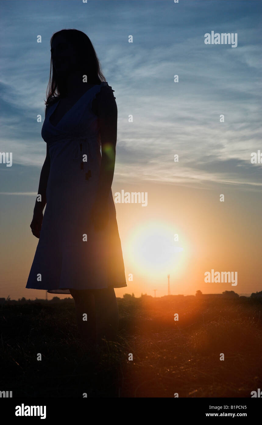 Silhouette of a young woman wearing summer dress standing in field at dusk sun shining behind - Stock Image