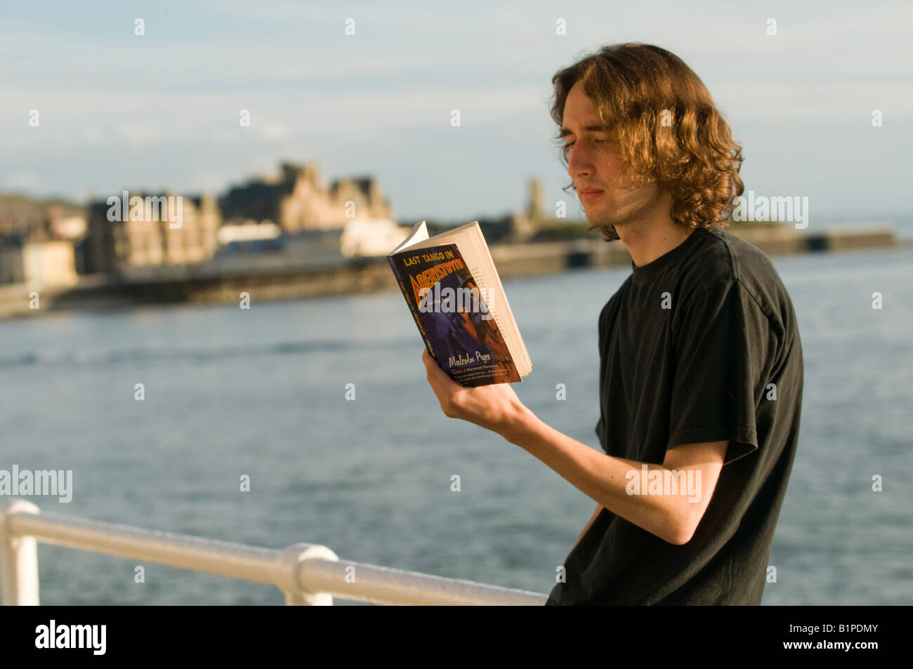 Young man reading  'Last Tango in Aberystwyth' by Malcolm Price on the promenade in Aberystwyth, summer - Stock Image
