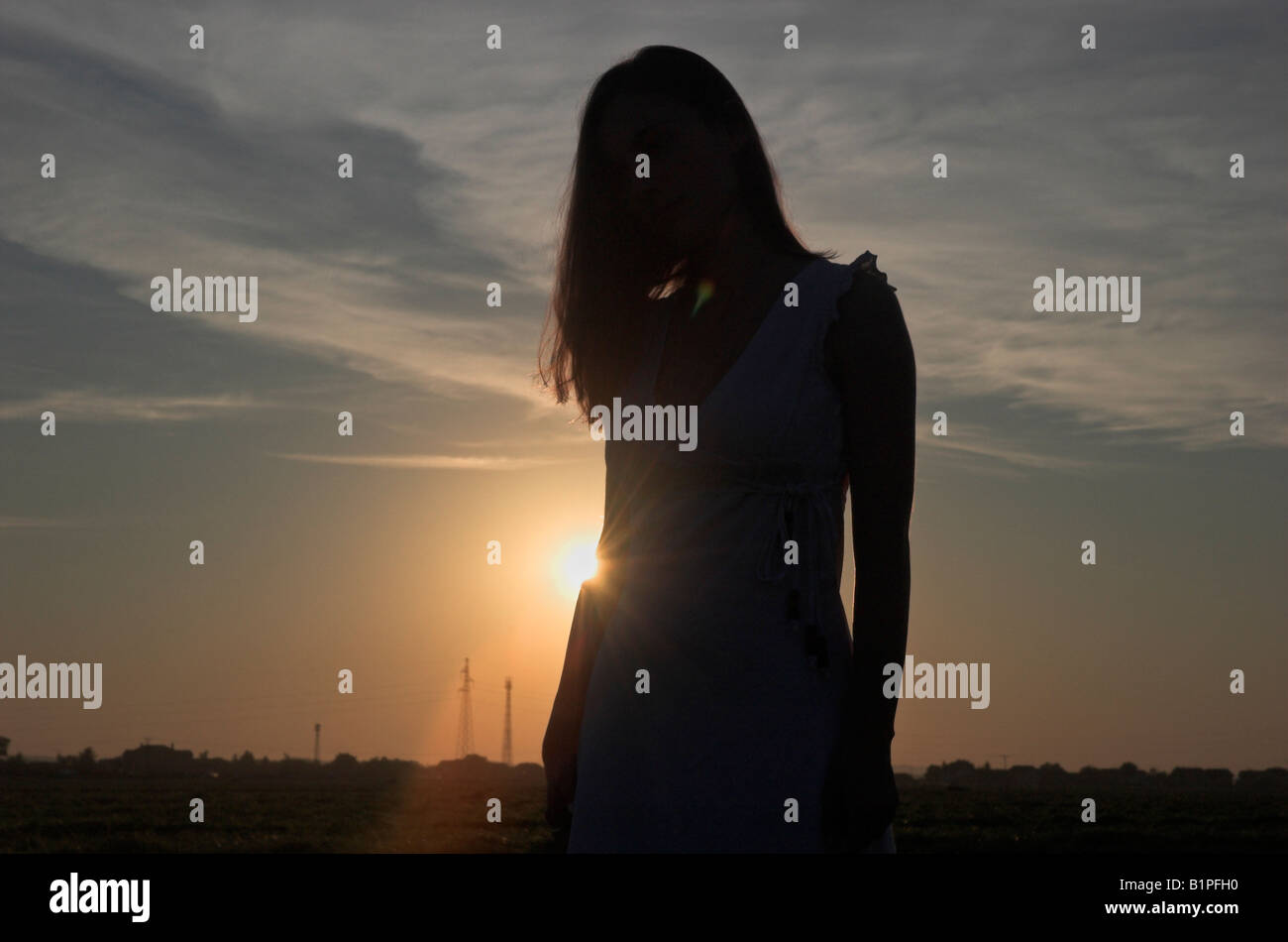 Silhouette of a young woman wearing summer dress standing outdoors at dusk sun shining behind head bowed - Stock Image
