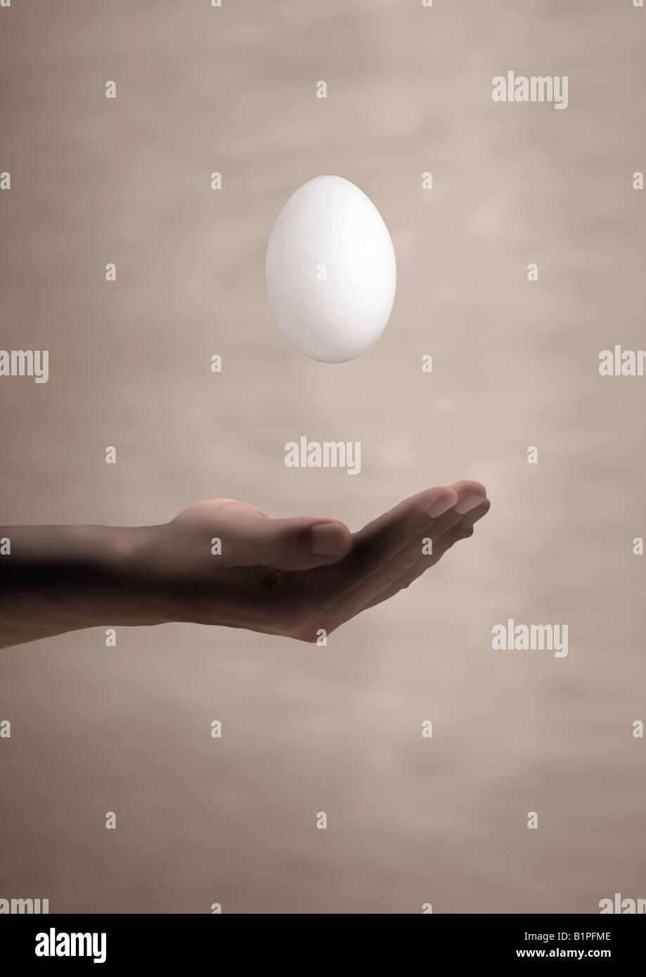 floating egg schwebendes fallendes Ei über einer Hand - Stock Image