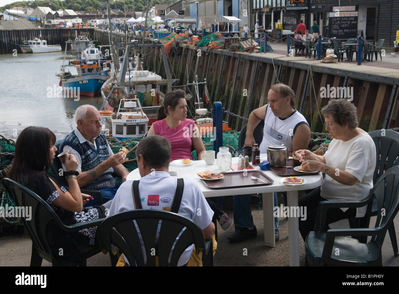 Whitstable family Oyster fishermen have breakfast at the harbour before the start of the Oyster Festival. Kent UK - Stock Image