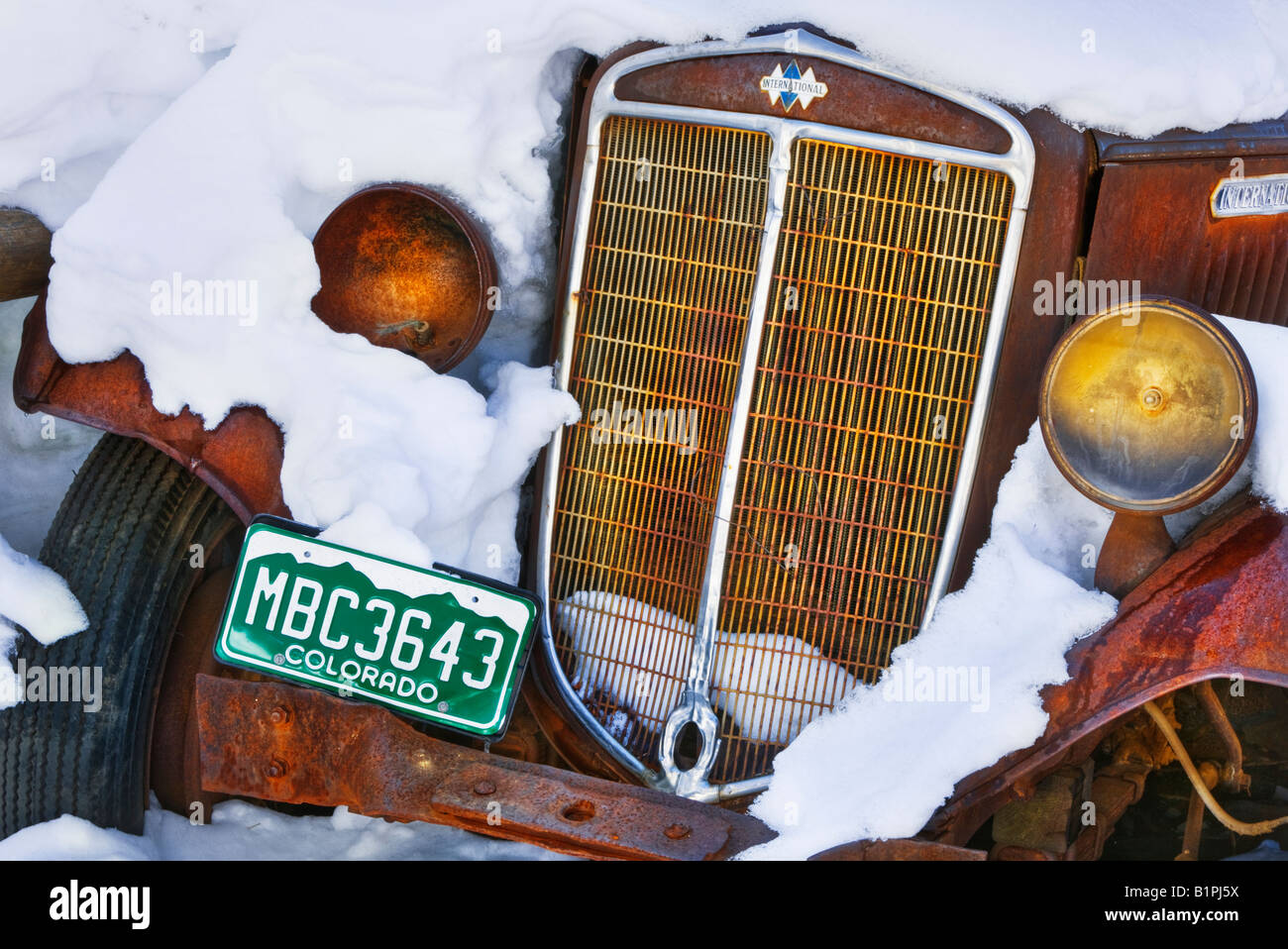A rusty old car covered in snow near Steamboat Springs, Colorado, USA. - Stock Image
