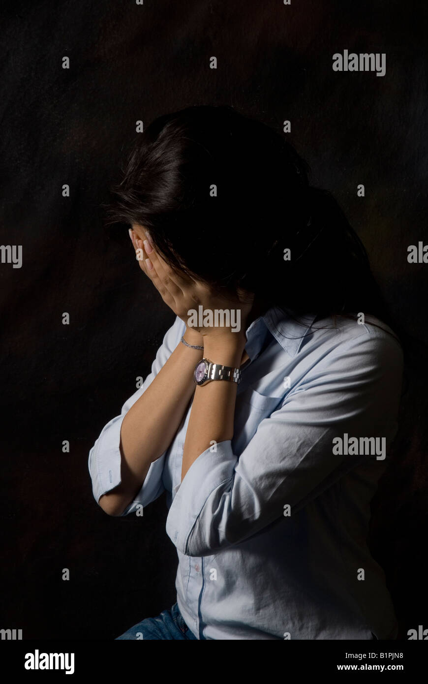 Depressed young woman head in hands against a black background - Stock Image