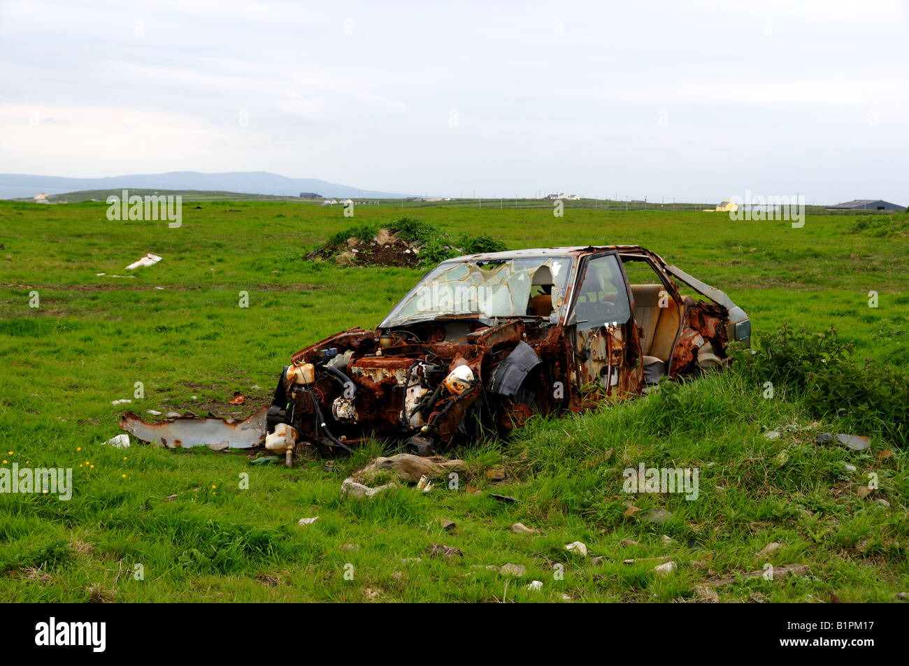 An abandoned car rusts in the open green field. County Clare, Ireland. - Stock Image