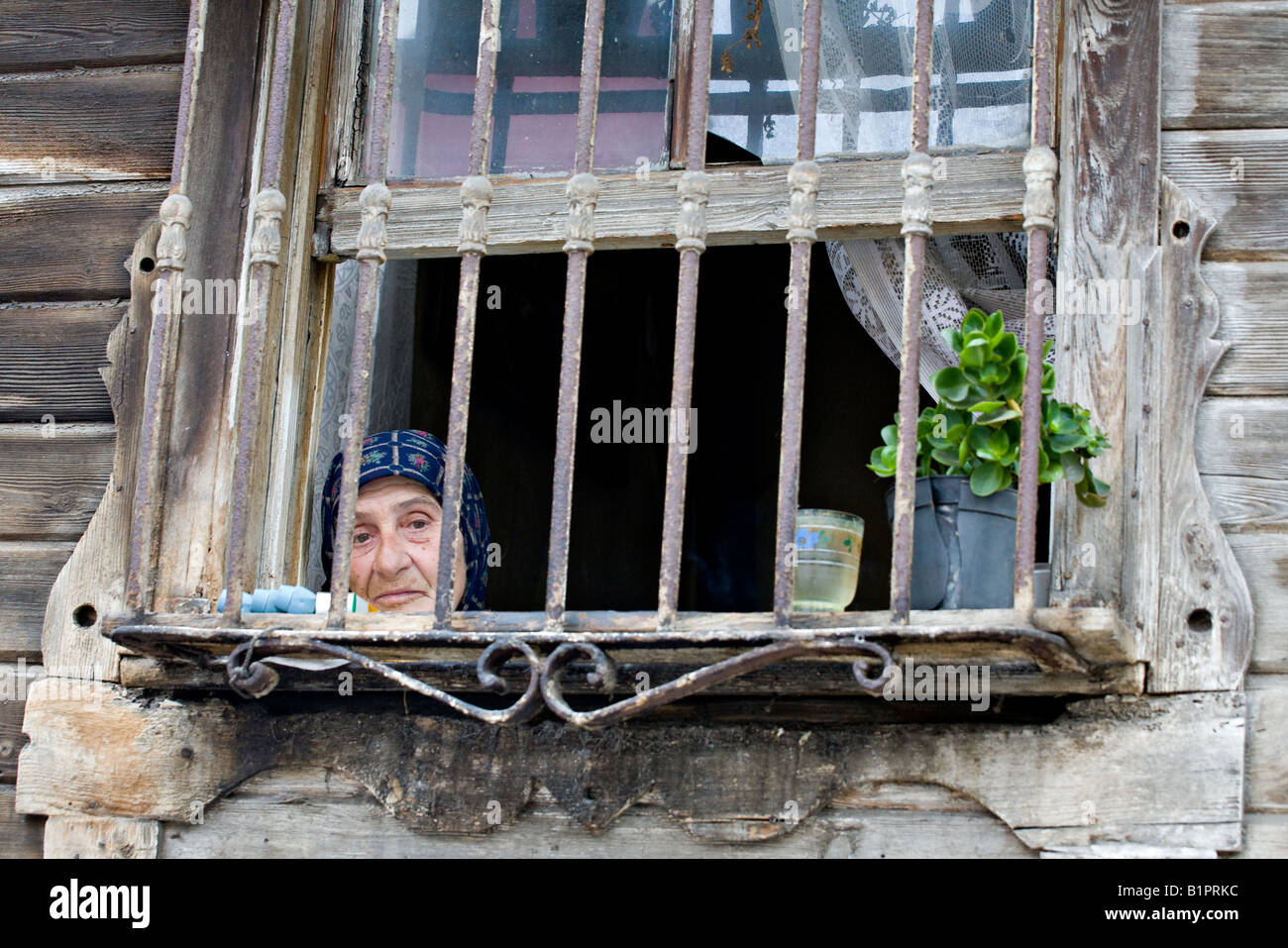 Yesilkoy Shut in An old woman looks out her iron barred window of her unpainted greying house into the streets - Stock Image