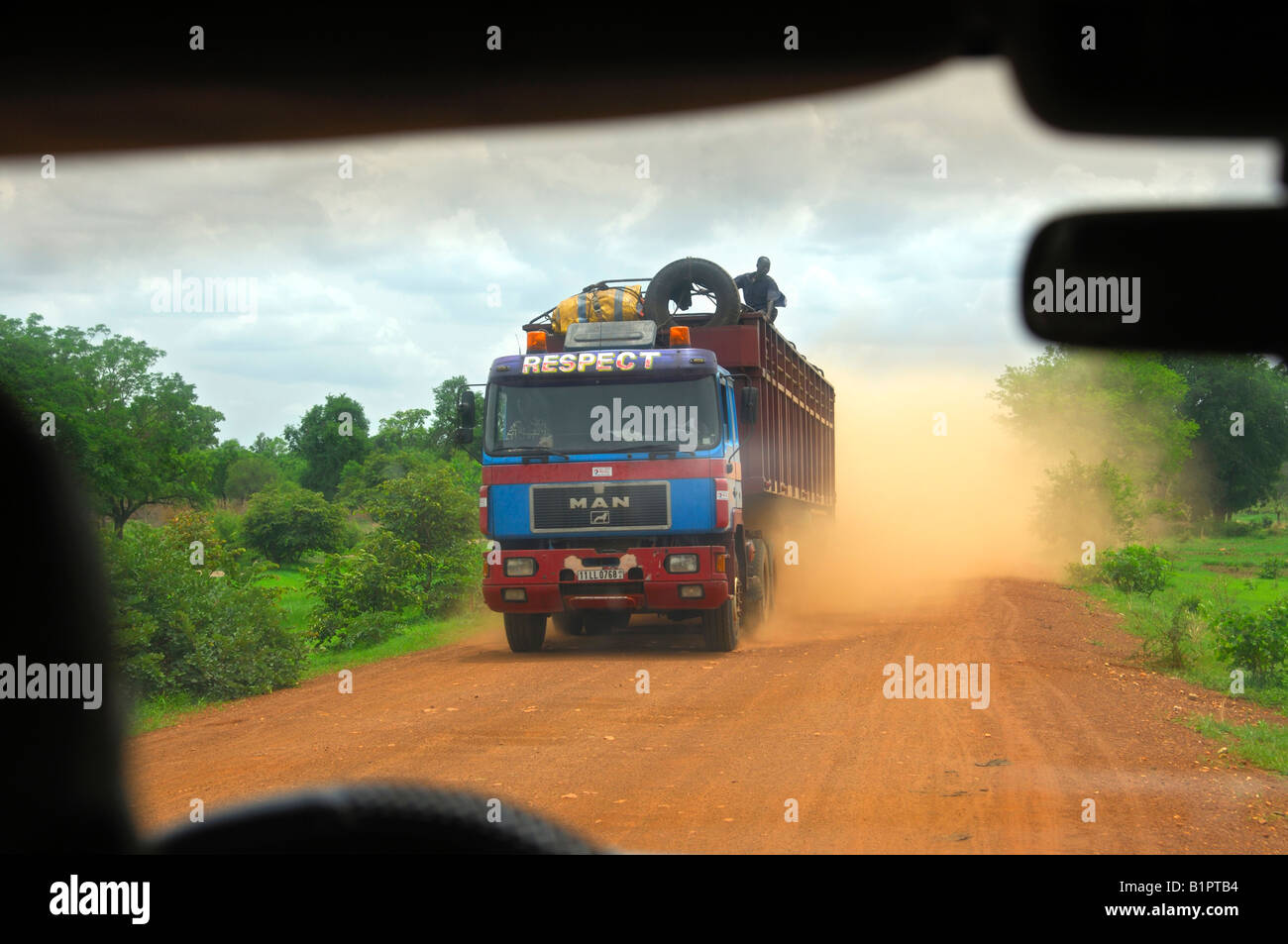 Heavy truck generates a large dust cloud on an unsurfaced country road, Burkina Faso - Stock Image
