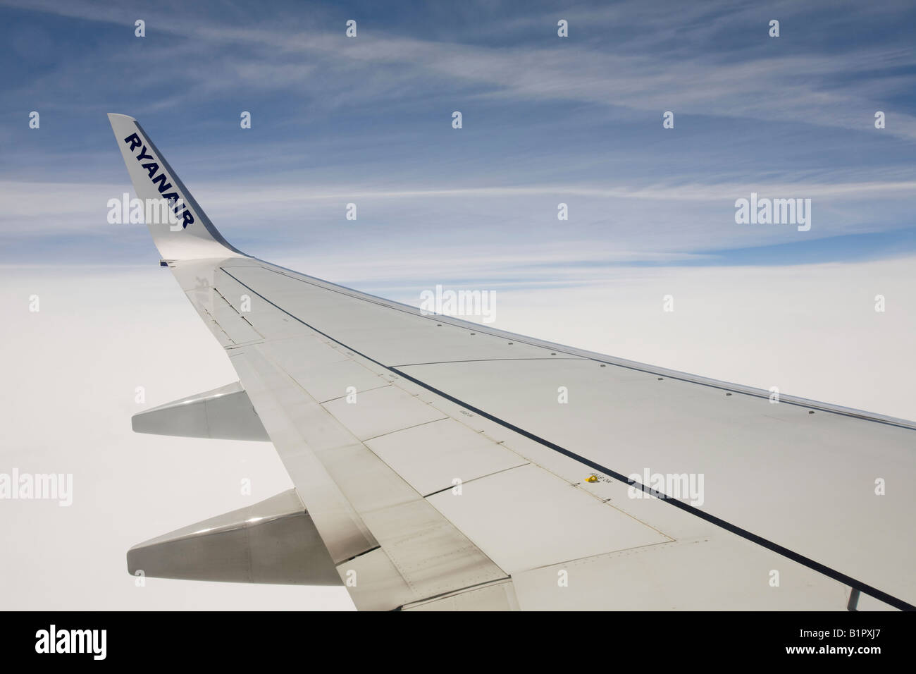 The wing of a Ryanair plane flying over the Alps with vapour trails Stock Photo