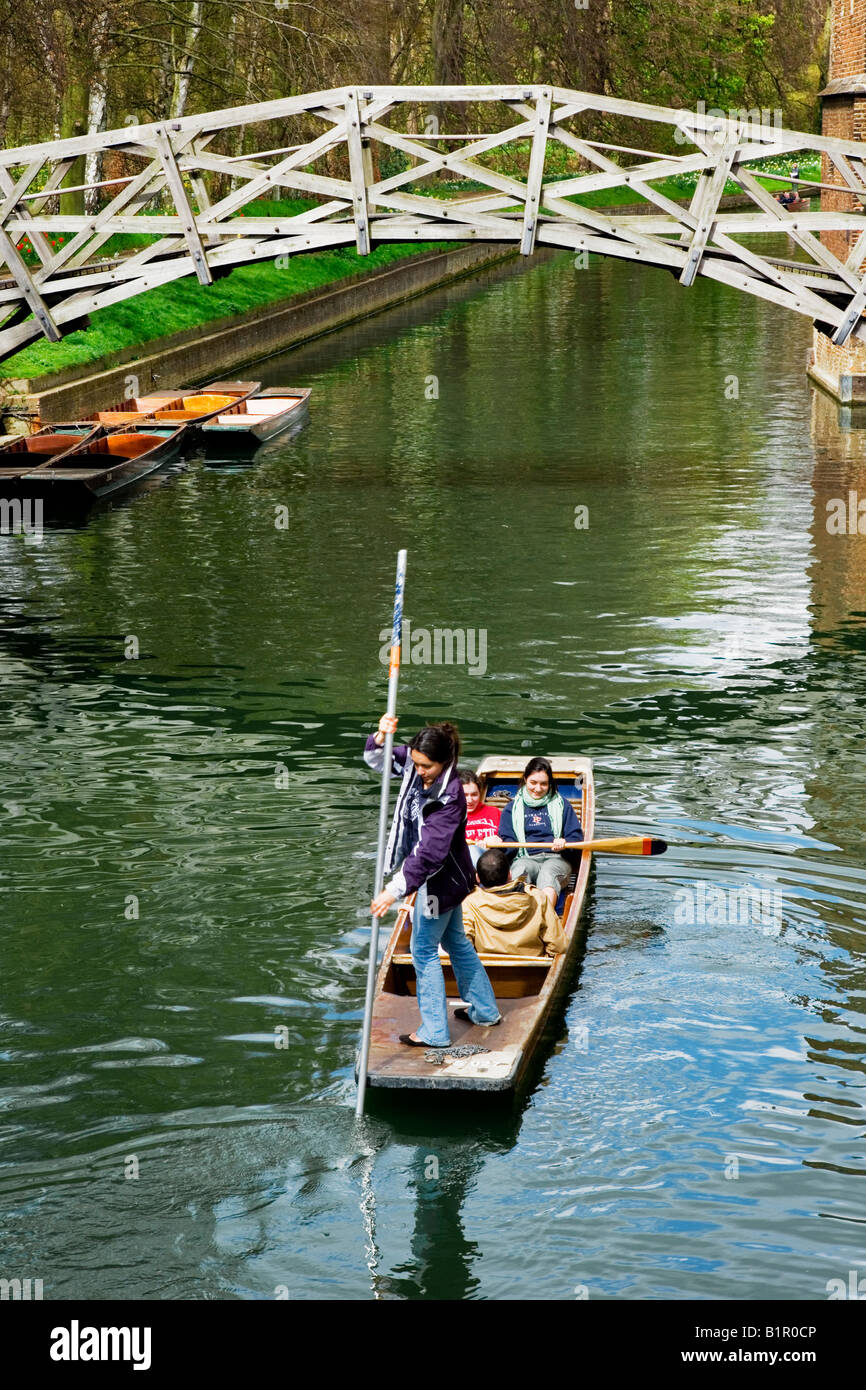 Young woman, girl, and her friends punting beneath the Mathematical Bridge over the River Cam at Queen's College, - Stock Image