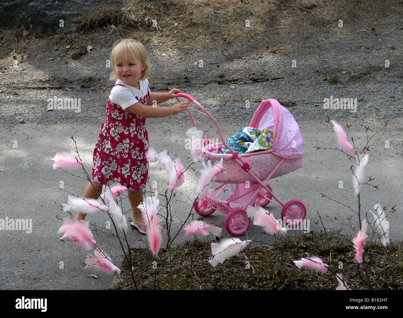 Small girl with dolls pram - Stock Image