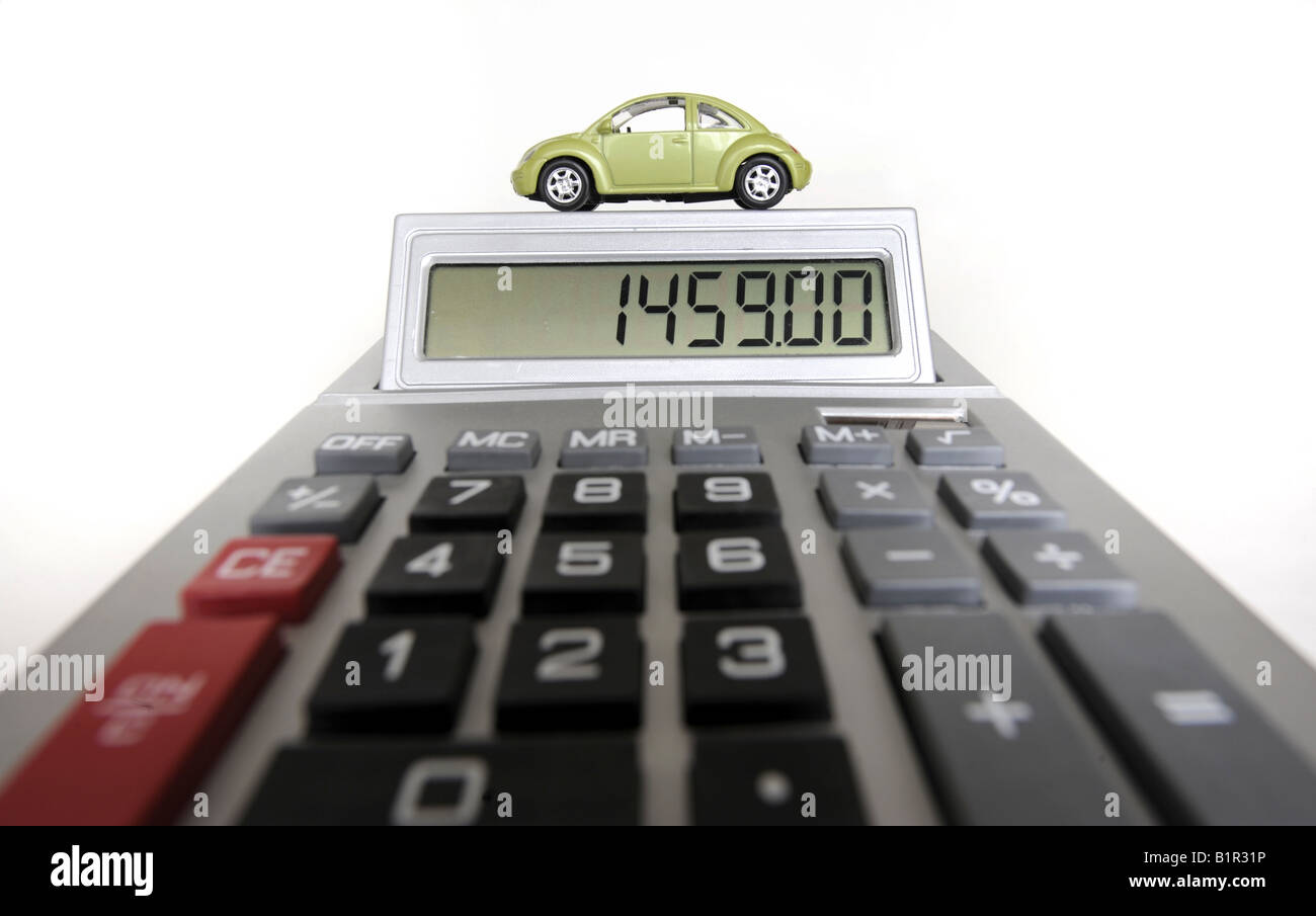 MODEL CAR ON CALCULATOR RE MOTORING COSTS REPAIRS HOUSEHOLD BUDGETS ETC UK Stock Photo