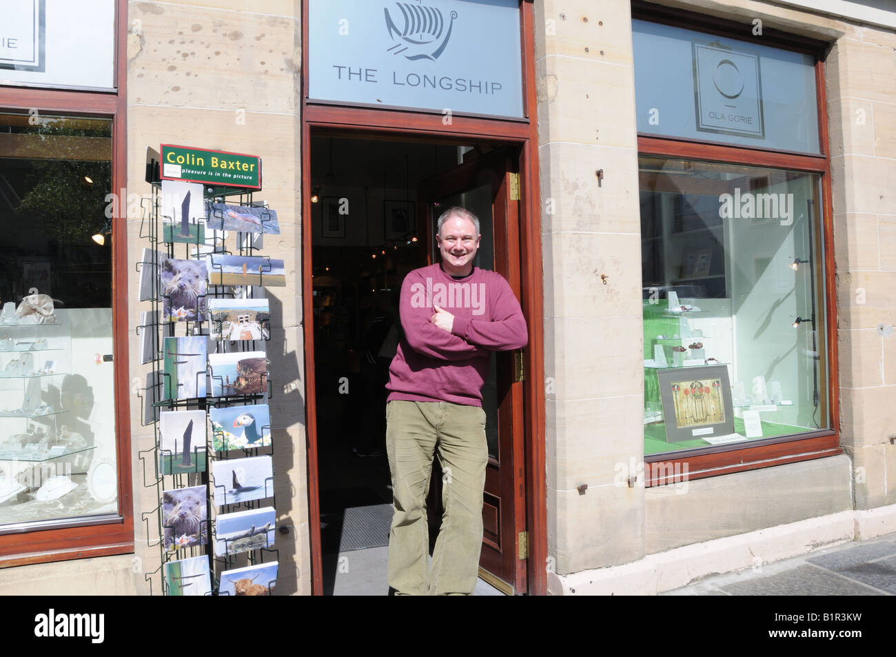 Writer, wine merchant and musician, Duncan McLean, standing at the door of the Longship — a gallery in Kirkwall, - Stock Image