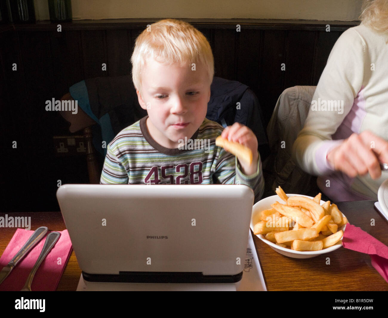 Young child / boy / kid watches / watching a TV film on a portable DVD player while eating chips. UK - Stock Image
